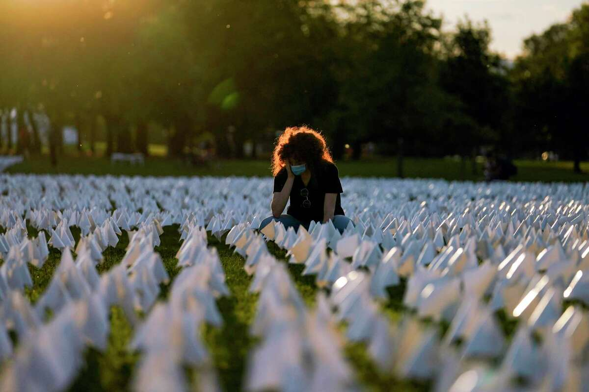 """Zoe Nassimoff pauses among the white flags representing Americans who have died of COVID-19 that are part of artist Suzanne Brennan Firstenberg's temporary art installation, """"In America: Remember,"""" on the National Mall in Washington, D.C., on Sept. 17."""