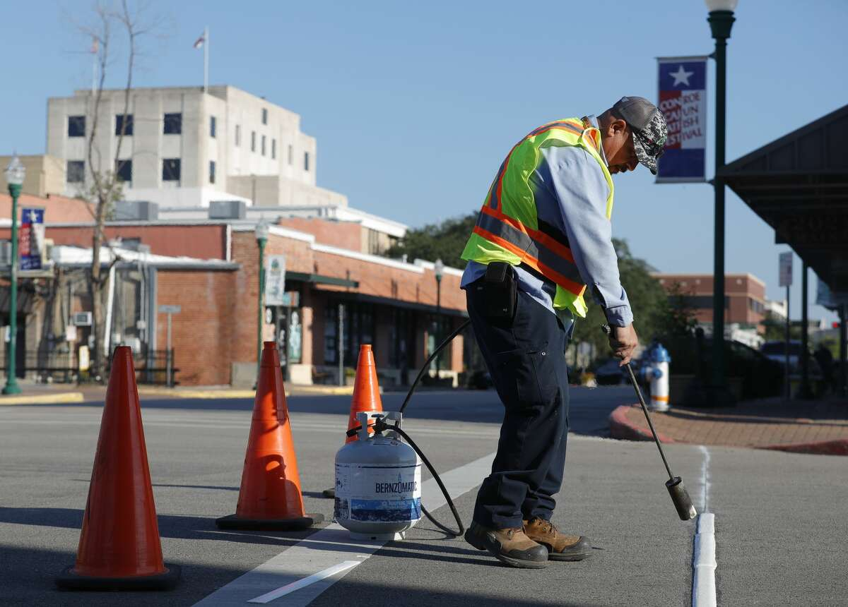 Conroe Public Works employee Alex Avila works to re-stripe walkways in downtown ahead of the start of the Conroe Cajun Catfish Festival, Wednesday, Oct. 6, 2021, in Conroe. The annual festival, which includes a full music lineup, games and food, begins Friday and runs through Sunday.
