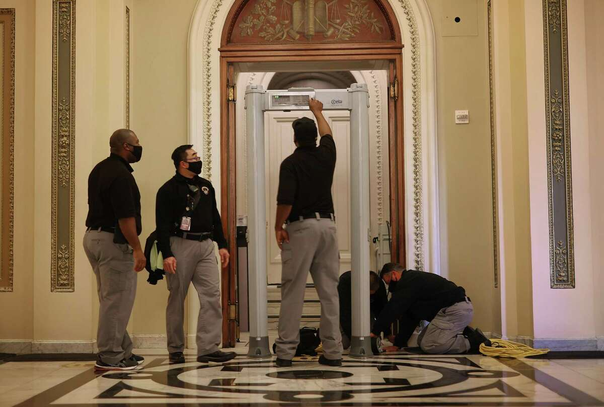 U.S. Capitol Police install a metal detector outside the House of Representatives Chamber, on the very spot where violent insurrectionists attempted to smash their way through and halt the certification of the Electoral College votes in Washington, DC. (Photo by Chip Somodevilla/Getty Images)