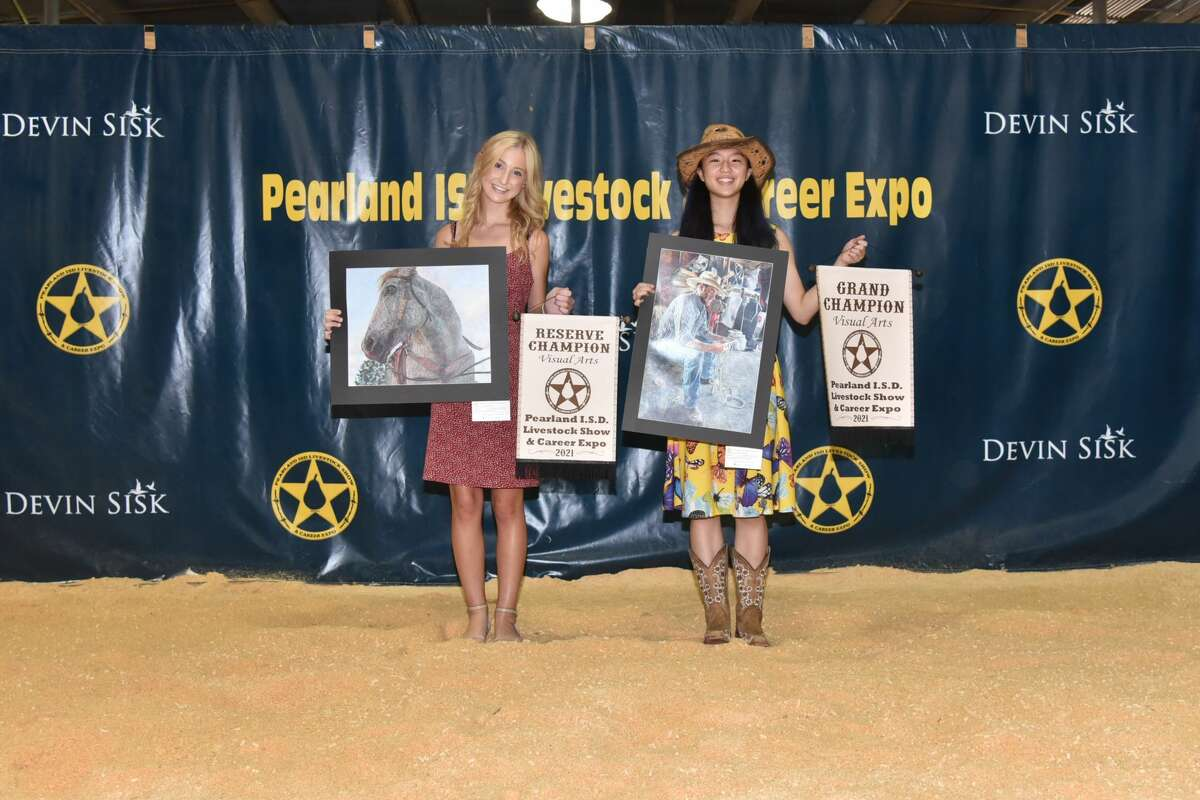 Dawson High School's Avery Gilman, left, and Faith Victoria Ni hold the artwork that earned them Reserve Champion and Grand Champion awards, respectively, at the 10th annual Pearland Independent School District Livestock Show & Career Expo.