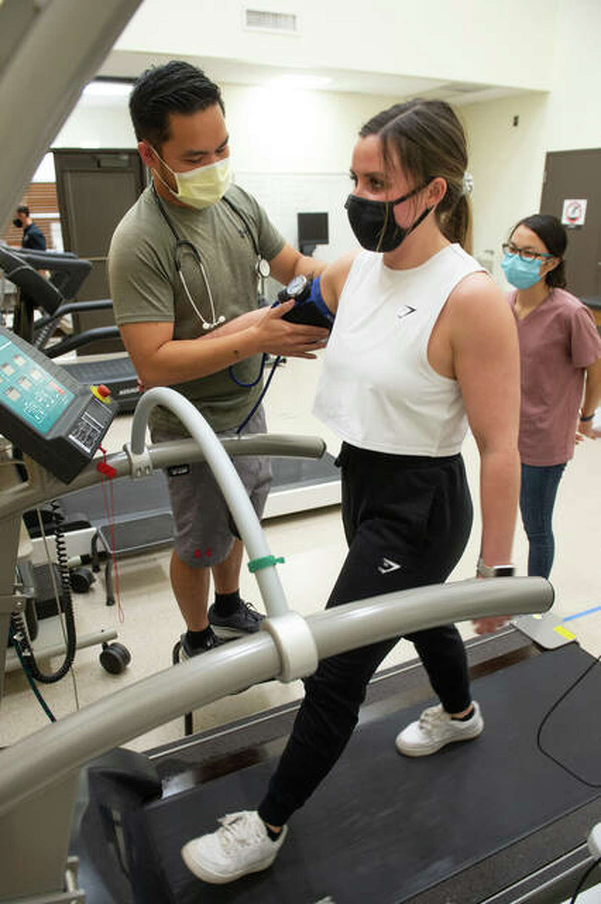 Graduate students Michael Ferreras, left, Jordan Killen, right, and Magali Coreggia. back, conduct heart rate and blood pressure while administering a graded exercise test at Southern Illinois University Edwardsville.