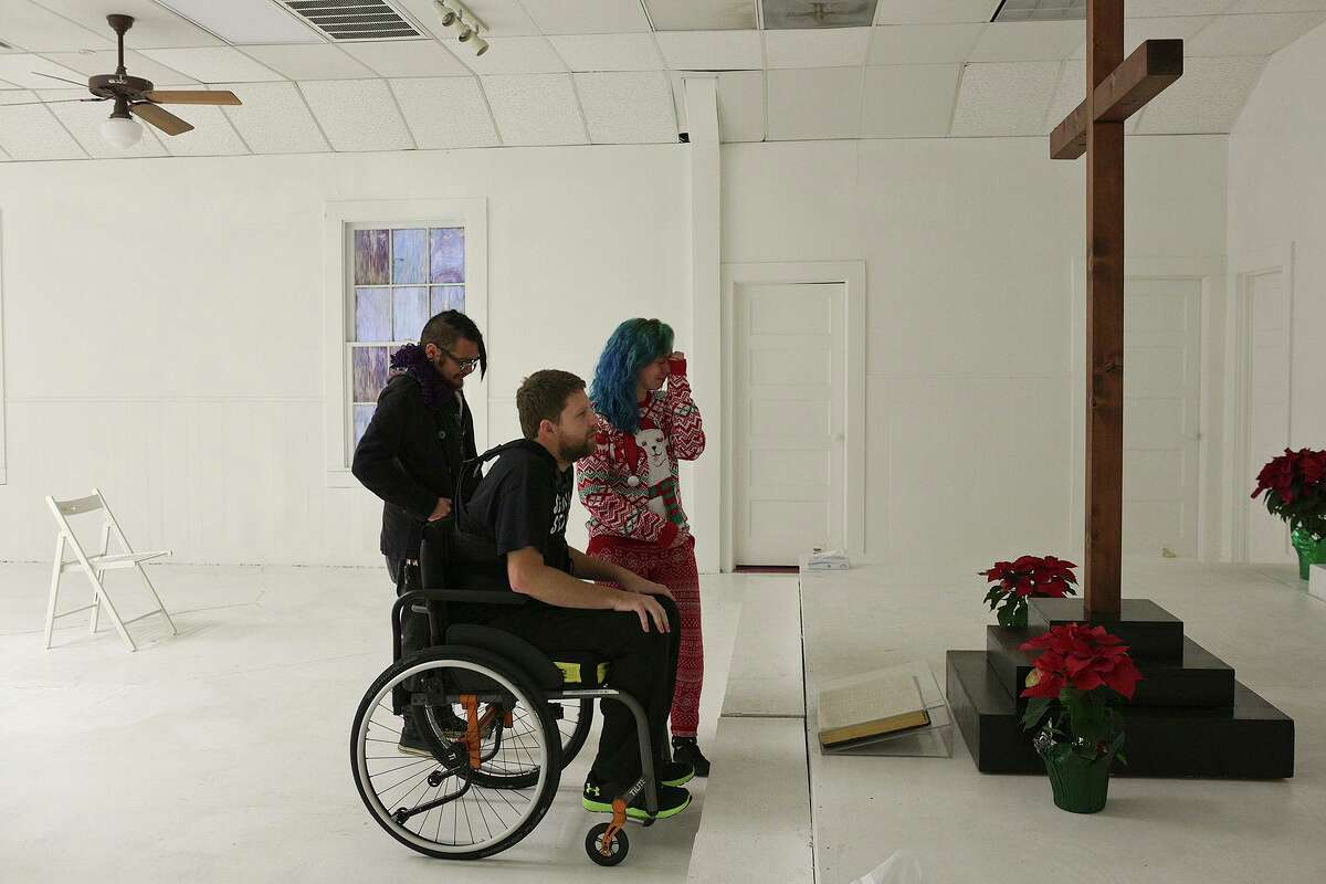 Kris Workman, with his wife, Colbey Workman, and friend Benny Ramirez, visits the memorial inside First Baptist Church in Sutherland Springs on Sunday, Dec. 17, 2017. The visit was Kris' first time back at the church since he was shot and paralyzed there Nov. 5.