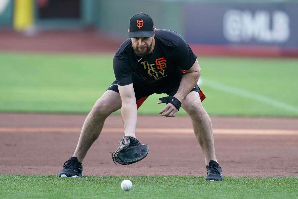 San Francisco Giants' Brandon Belt fields ground balls during a baseball practice in San Francisco, Tuesday, Oct. 5, 2021. (AP Photo/Jeff Chiu)