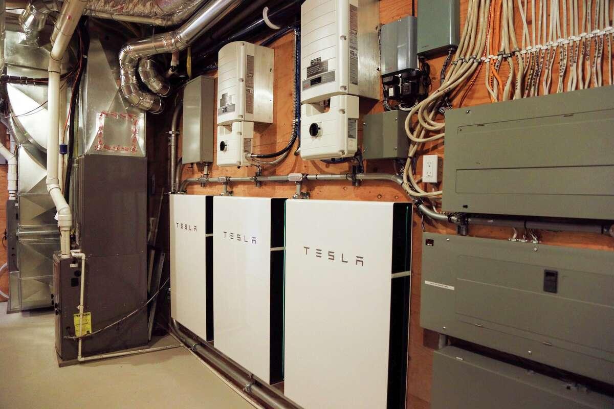 Tesla PowerWall batteries are seen in a home garage.