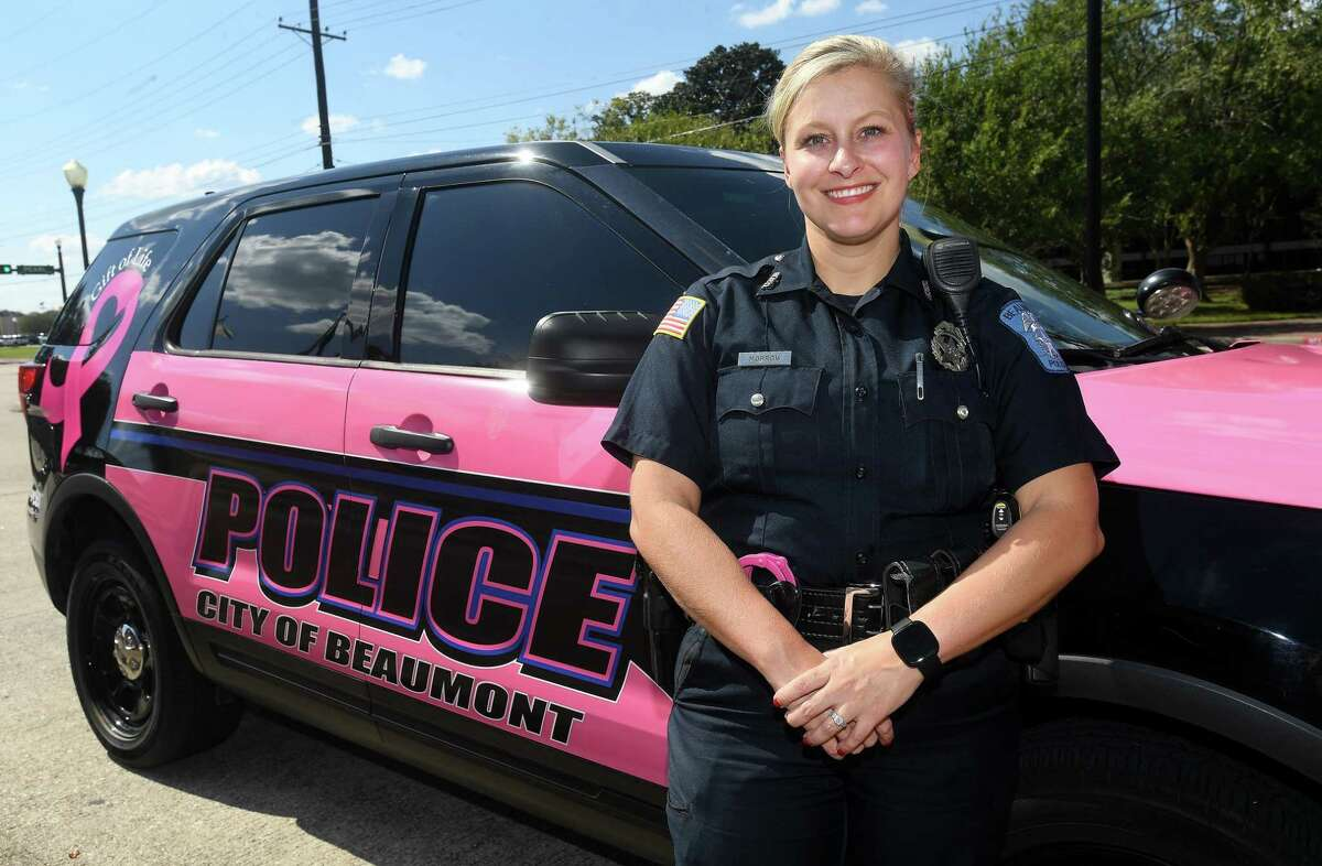 Beaumont Police officer Haley Morrow stands with the newly wrapped pink patrol car to raise awareness for Gift of Life and Breast Cancer Awareness Month. The department gets a vehicle wrapped for the month of October every year, and it will make its appearance at community events where the public can add personal messages to honor survivors and loved ones lost. Photo made Wednesday, October 6, 2021 Kim Brent/The Enterprise