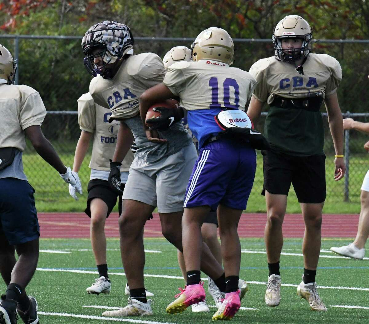 Christian Brothers Academy running back/middle linebacker Jaylen Riggins, center, tries to strip the ball from a teammate during a practice session on Wednesday, Oct. 6, 2021, at CBA in Colonie, N.Y.