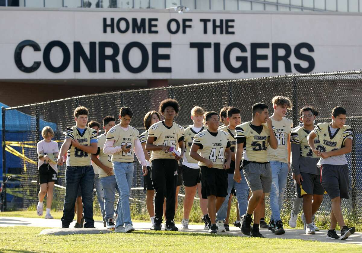 Football players walk toward the staging area for Conroe High School's homecoming parade, Wednesday, Oct. 6, 2021, in Conroe. The school's football team will host Oak Ridge at Buddy Moorhead Stadium on Friday for it's homecoming game.