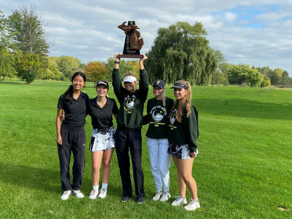 Dow High's (from left) Joline Che, Kylie Keefer, Abby Wilson, Abbey Ieuter, and Paige Barnard pose with the championship trophy after winning Wednesday's Division 2 regional at Saginaw Public Golf Course.