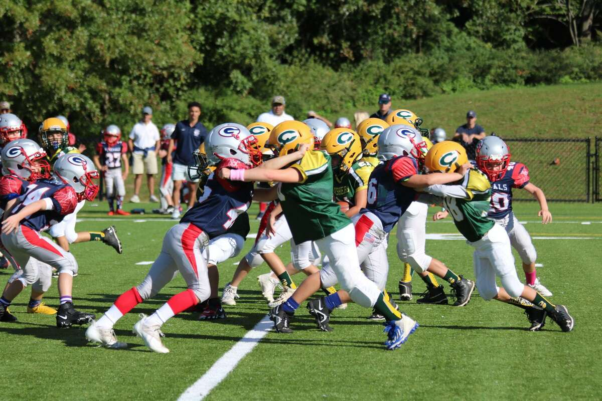 The Bantam Cos Cob Crushers offensive line opens up a hole for Joey Prisinzano (21) to run through.