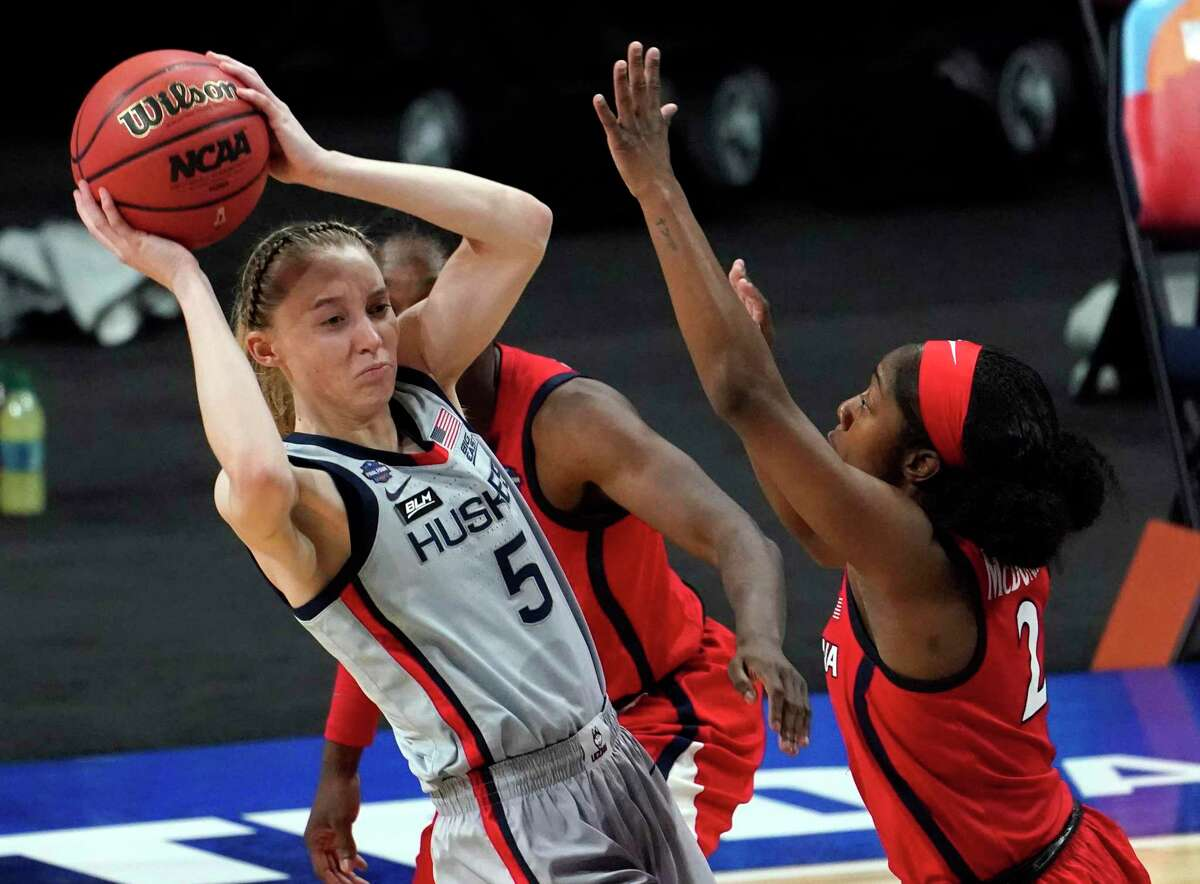 FILE - In this April 2, 2021, file photo, Connecticut guard Paige Bueckers (5) passes the ball over Arizona guard Aari McDonald (2) during the first half of a semifinal in the NCAA women's college basketball tournament Final Four at the Alamodome in San Antonio. As college athletes like Bueckers begin making money from the use of their names, images and likenesses, concerns are being raised over how the new rules will affect team chemistry. (AP Photo/Eric Gay, File)