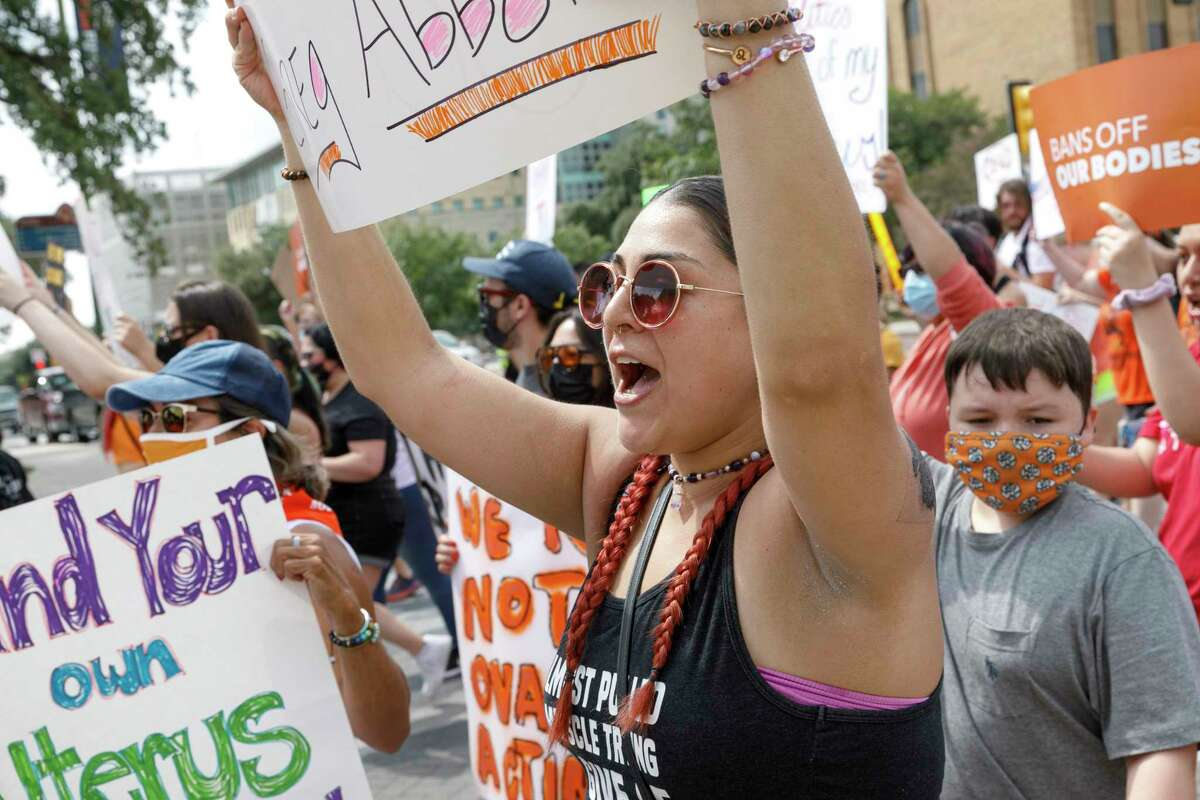 """Lauren Flores chants along with other protesters as they march through downtown San Antonio, Texas, Saturday, Oct. 2, 2021, while participating in the """"Ban Off Our Bodies"""" abortion rights march. It was one of more than 600 planned abortion rights marches taking place in cities across all 50 states Saturday afternoon."""