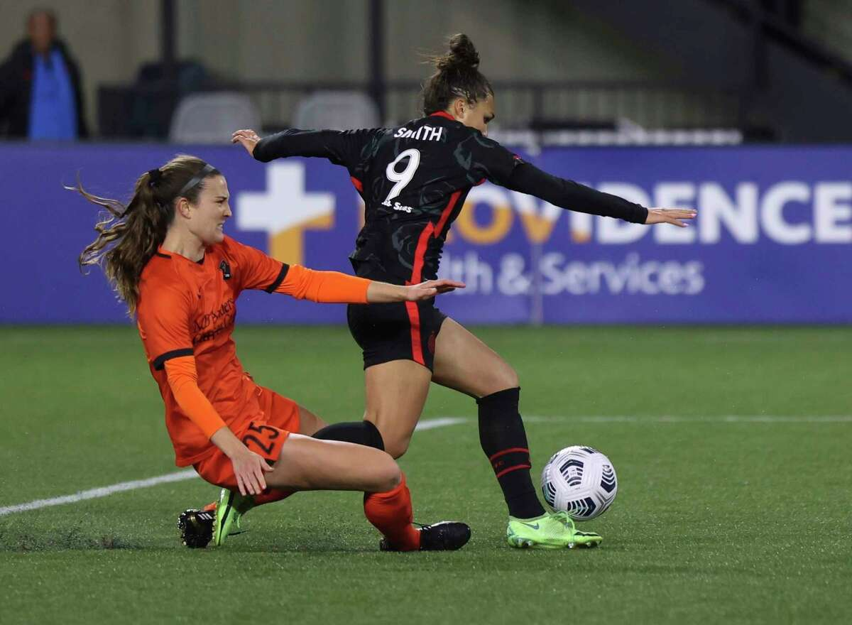 Portland Thorns forward Sophia Smith, right, shoots as Dash defender Katie Naughton slides for a tackle during the second half of an NWSL match Wednesday in Portland, Ore.