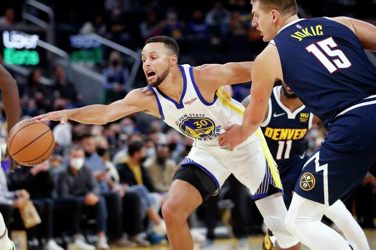 Golden State Warriors' Stephen Curry reaches for the ball against Denver Nuggets' Nikola Jokic in 1st quarter during NBA preseason game at Chase Center in San Francisco, Calif., on Wednesday, October 6, 2021.