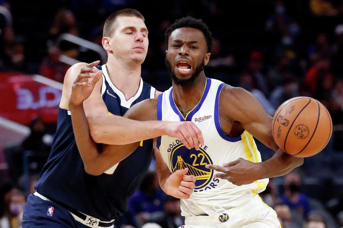 Golden State Warriors' Andrew Wiggins is fouled by Denver Nuggets' Nikola Jokic in 1st quarter during NBA preseason game at Chase Center in San Francisco, Calif., on Wednesday, October 6, 2021.