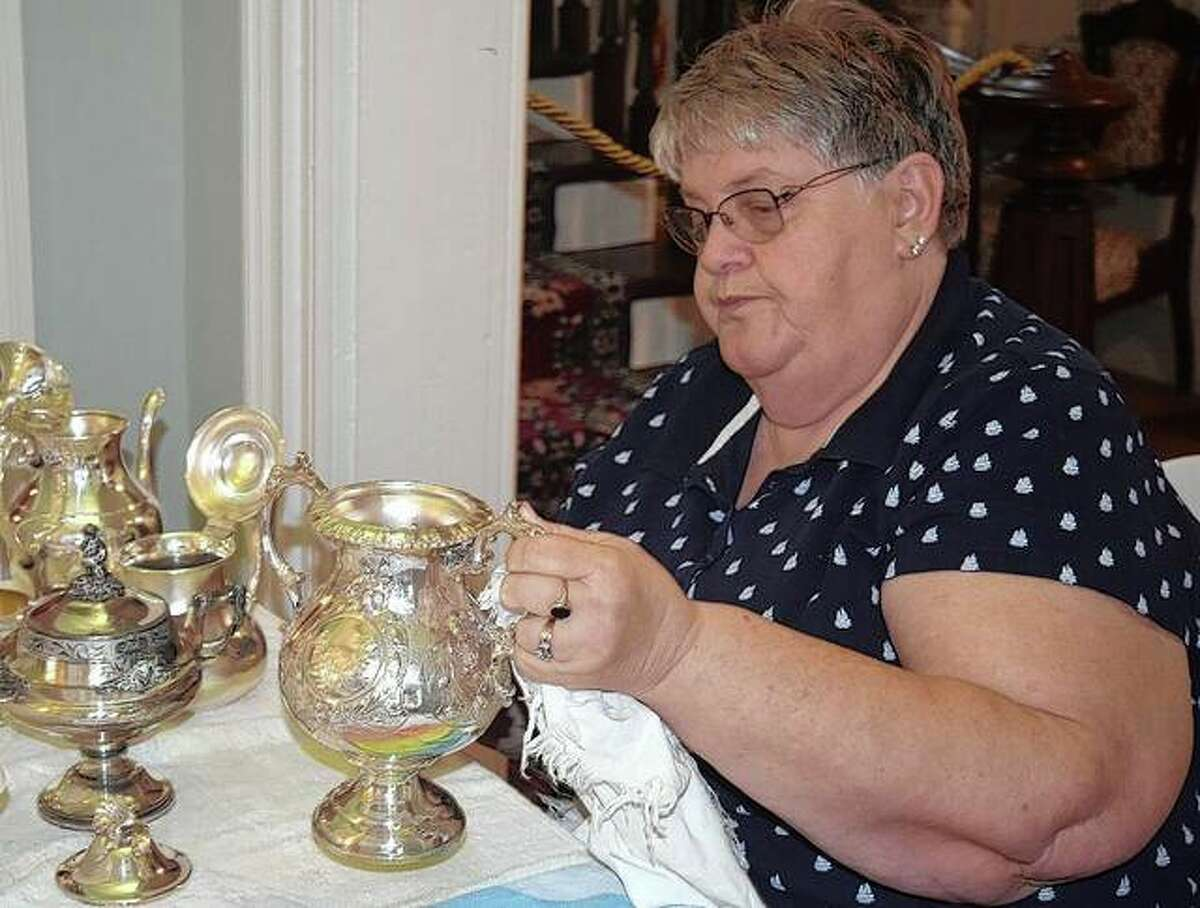 Susan Hardin polishes silver Wednesday at the Governor Duncan Mansion in preparation for an open house.