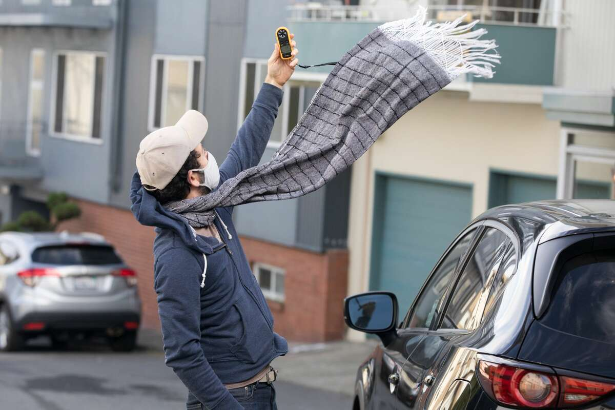 SFGATE editor Dan Gentile uses a wind-reading meter near Burnett Avenue and Crestline Drive in search of the windiest street in San Francisco on Oct. 6, 2021.