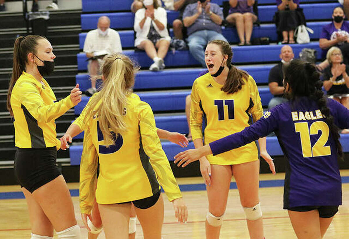 CM's Lauren Dunlap (11), shown celebrating a point during an Eagles win at August's Roxana Tourney, had nine kills Wednesday night in a win over Marquette Catholic in Bethalto.
