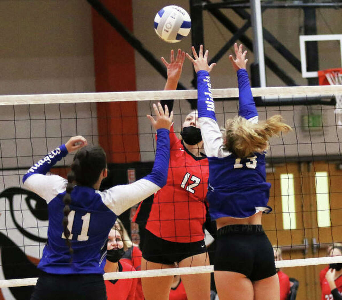 Staunton's Haris Legendre (middle) tips over a Freeburg block during a Labor Day Weekend tournament in Edwardsville. The Bulldogs won their 21st SCC game in a row Wednesday with a three-set victory over Vandalia in Staunton.