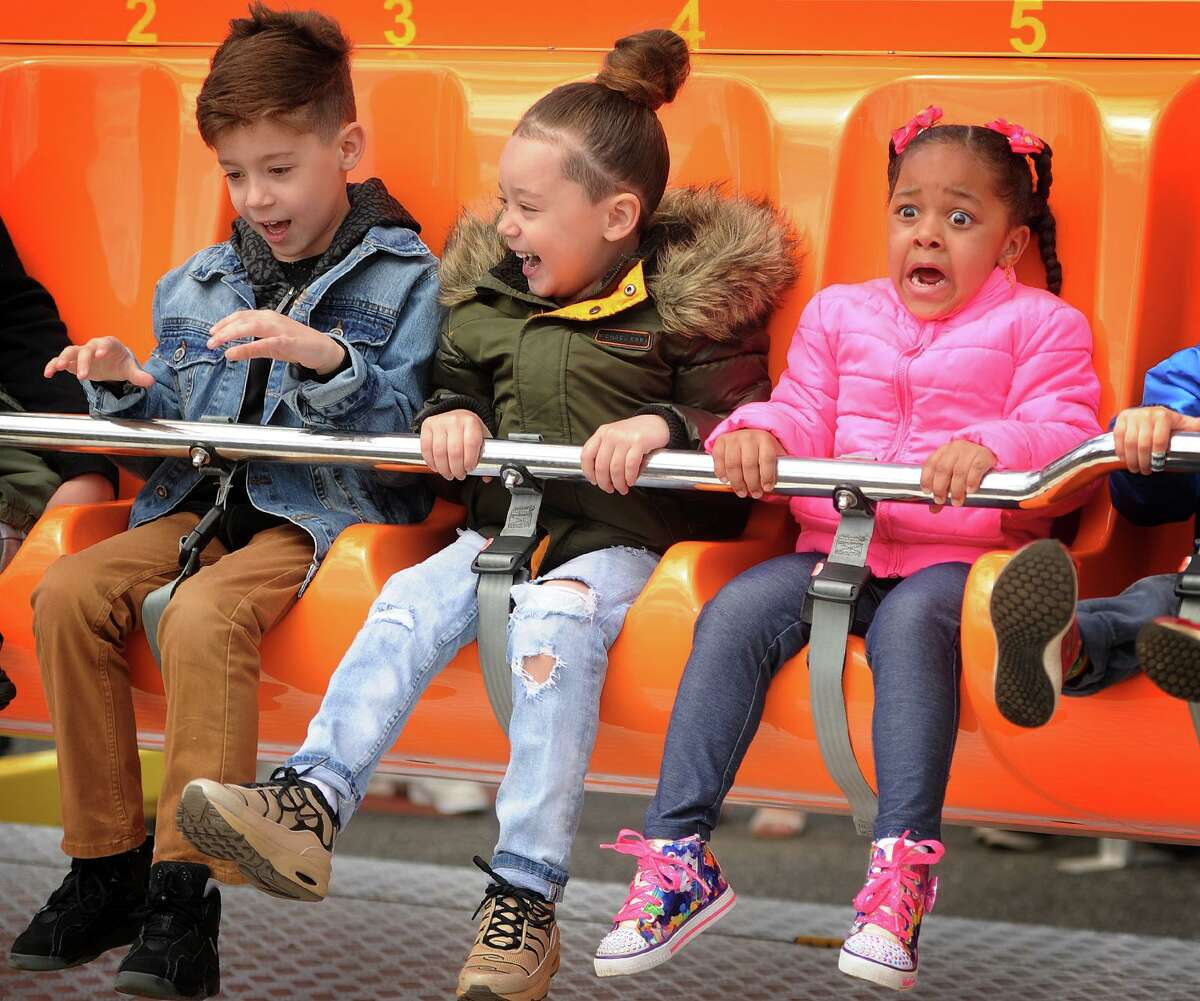 From left; Brandon Rodriguez, 7, Cayson Rodriguez, 5, and Brianna Lopez, 4, all of Bridgeport, have differing reactions as they go on one of the rides at the McKinley Elementary School Carnival at Jennings Beach in Fairfield, during a recent year. The McKinley Elementary School Carnival community-wide event is returning to Fairfield Oct. 22, through Oct. 24, after a two year hiatus because of the coronavirus pandemic. The event will be open from 6 to 10 p.m., Oct. 22, 1 to 10 p.m., Oct. 23, and 1 to 5 p.m., Oct. 24.