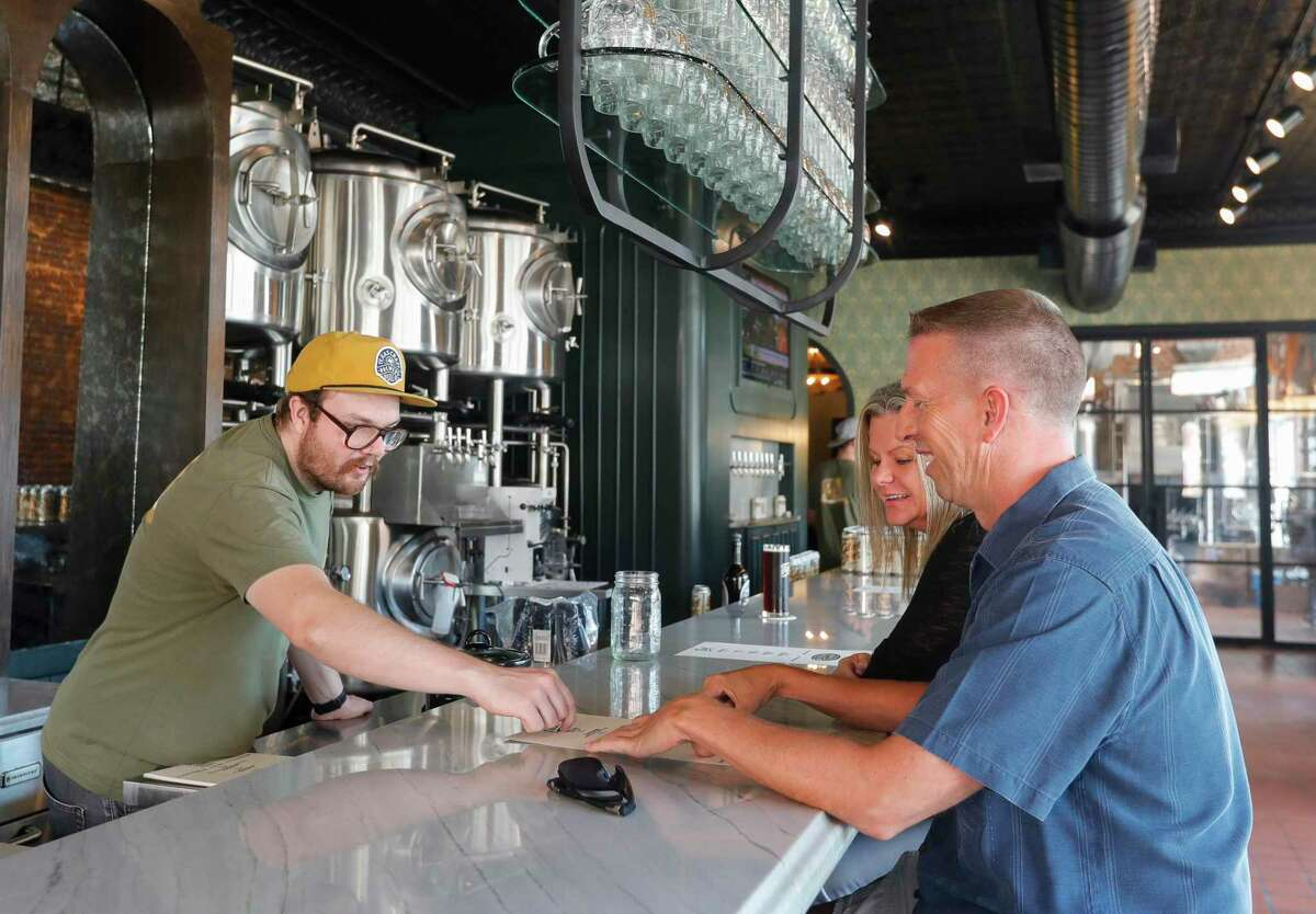 Dylan Emmons, co-owner of Fass Brewery, helps Chris Stamm and his wife, Janis, select from the beer menu, Wednesday, Oct. 6, 2021, in Conroe. The brewery opened up recently in one of the city's historic downtown buildings at Main Street and Simonton Street.