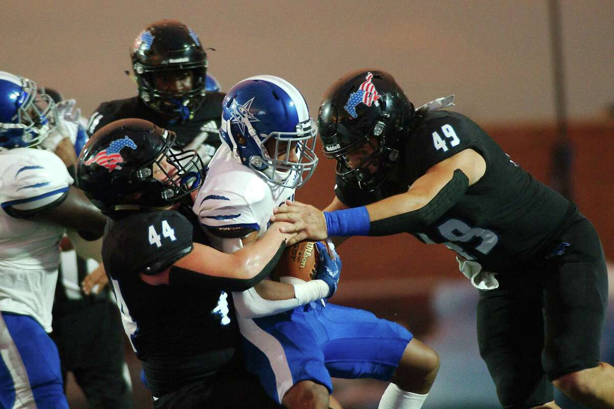 Baytown Sterling's Kody Arceneaux (7) is hit hard by Friendswood's Jaxson Russo (44) and Matthew Reyes (49) Friday at Friendswood High School. The Mustangs travel Friday to play Beaumont United.