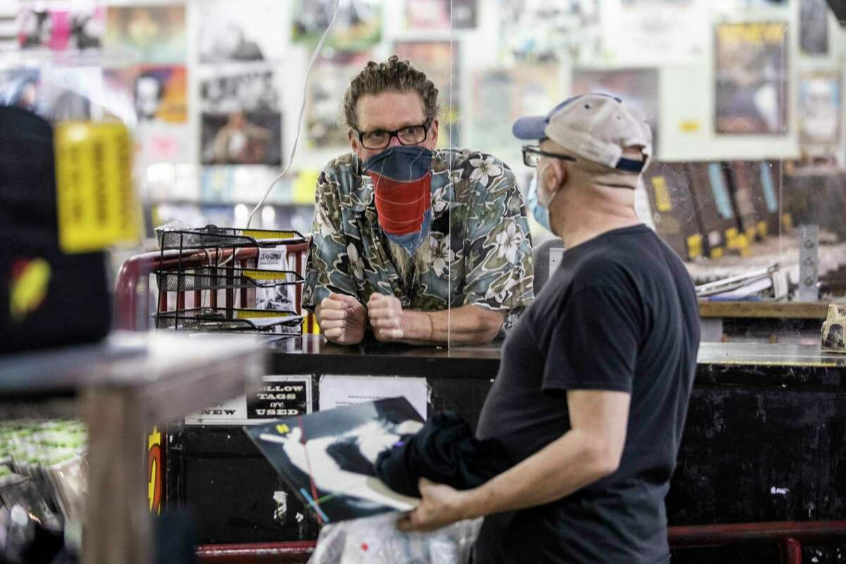 Ryan Boucher of Amoeba Music (left) converses with a customer at the Haight-Ashbury store. Bay Area residents have generally been supportive of mask rules, but fatigue is rising.