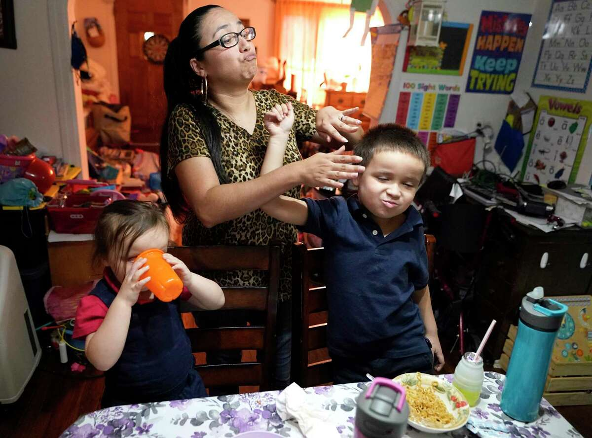 """Yrsa Becker, 4, left, her mother, Brittaney, and her bother, Malachi, 6, have a playful exchange while they eat dinner. """"Any little thing helps,"""" Brittaney said about the expanded child tax credit."""