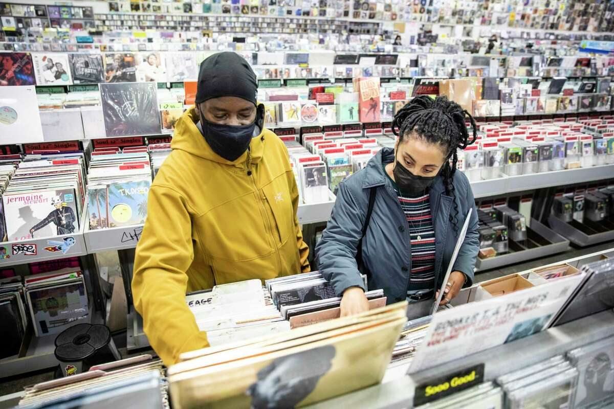 JC Cullars of Atlanta and daughter Nina shop for vinyl records at Amoeba Music in San Francisco on Wednesday. Masks will still be required in stores, but on Oct. 15, gyms, offices and a few other types of venues where only vaccinated people gather can ease off mask rules.
