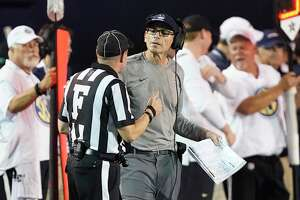 Connecticut head coach Lou Spanos talks to field judge Jay Brown in the first half of an NCAA college football game between Connecticut and Vanderbilt Saturday, Oct. 2, 2021, in Nashville, Tenn. (AP Photo/Mark Humphrey)