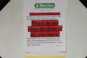 COVID-19 testing signs are seen inside the front door in Marra's Pharmacy on Thursday, Oct, 7, 2021 in Cohoes, N.Y.