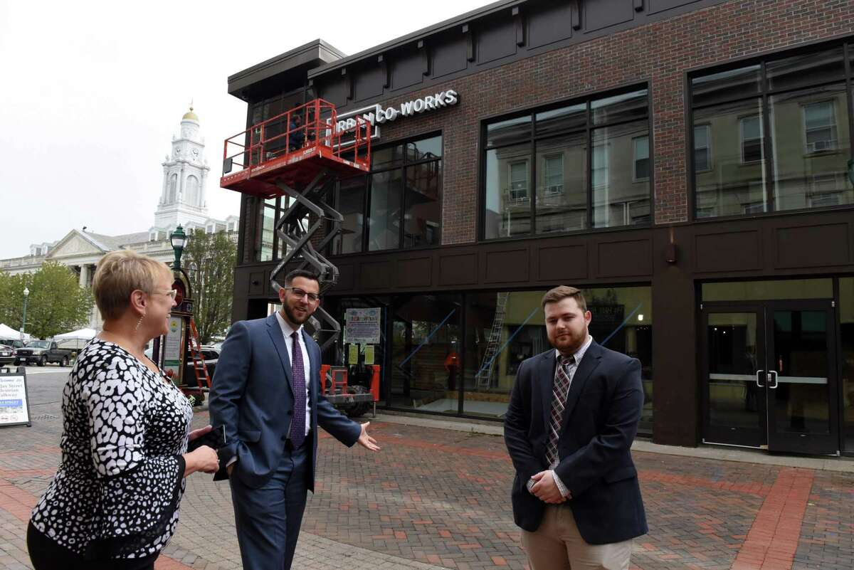 Sam Thompson, principal broker of a Schenectady-based realty agency, and Thompson Real Estate Team members, realtors Tracy Thompson, left, and Ean Ross, right, stand outside the Urban Co-Works co-working space where Thompson moved after the pandemic on Thursday, Oct. 7, 2021, in Schenectady, N.Y. Thomson formerly rented a traditional business office.