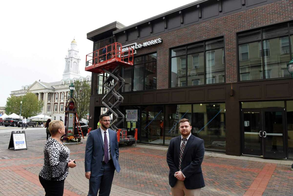 Sam Thompson, principal broker of a Schenectady-based realty agency, and Thompson Real Estate Team members Tracy Thompson, left, and Ean Ross, right, stand outside the Urban Co-Works coworking space where Thompson moved after the pandemic on Thursday, Oct. 7, 2021, in Schenectady, N.Y. Thomson formerly rented a traditional business office.