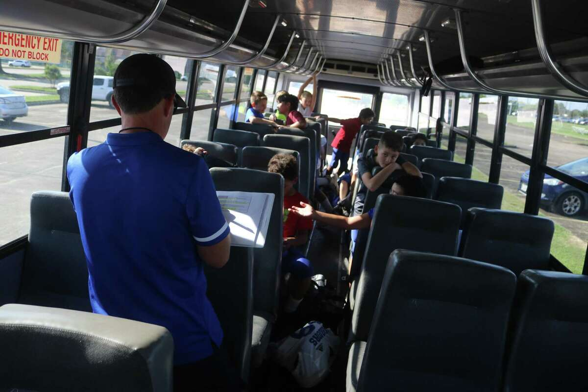 Coach Jared Buchanan takes roll call of his fifth and sixth-grade football players inside the team bus, before departing for their trip to Lutheran South.