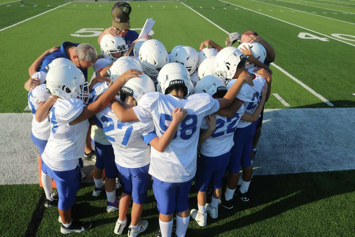 FBCA's elementary school football team holds a prayer before their contest at Glassell Stadium.