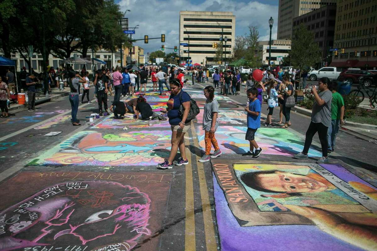 People walk past chalk art pieces during Chalk It Up on Oct. 13, 2018, on Main Avenue in downtown San Antonio. The annual event gives artists and regular folk the chance to make art along the sidewalks and in the road on Houston Street and Main Avenue.