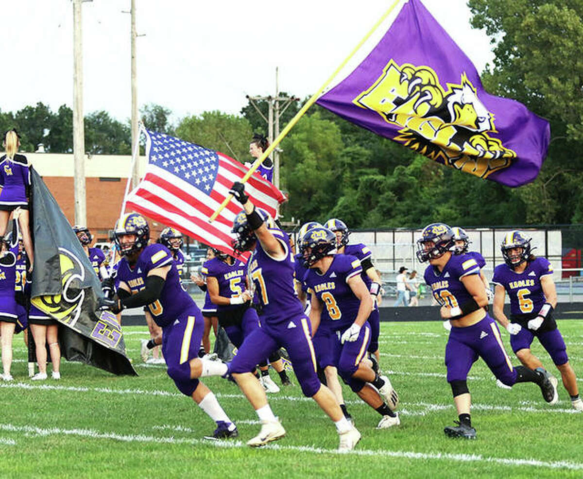 CM's Melvin Hodge (U.S. flag) and Cole Stimac (CM flag) lead the Eagles onto the field before a Sept. 10 game against Roxana at Hauser Field in Bethalto. The Eagles are back home Friday to play unbeaten Mascoutah.