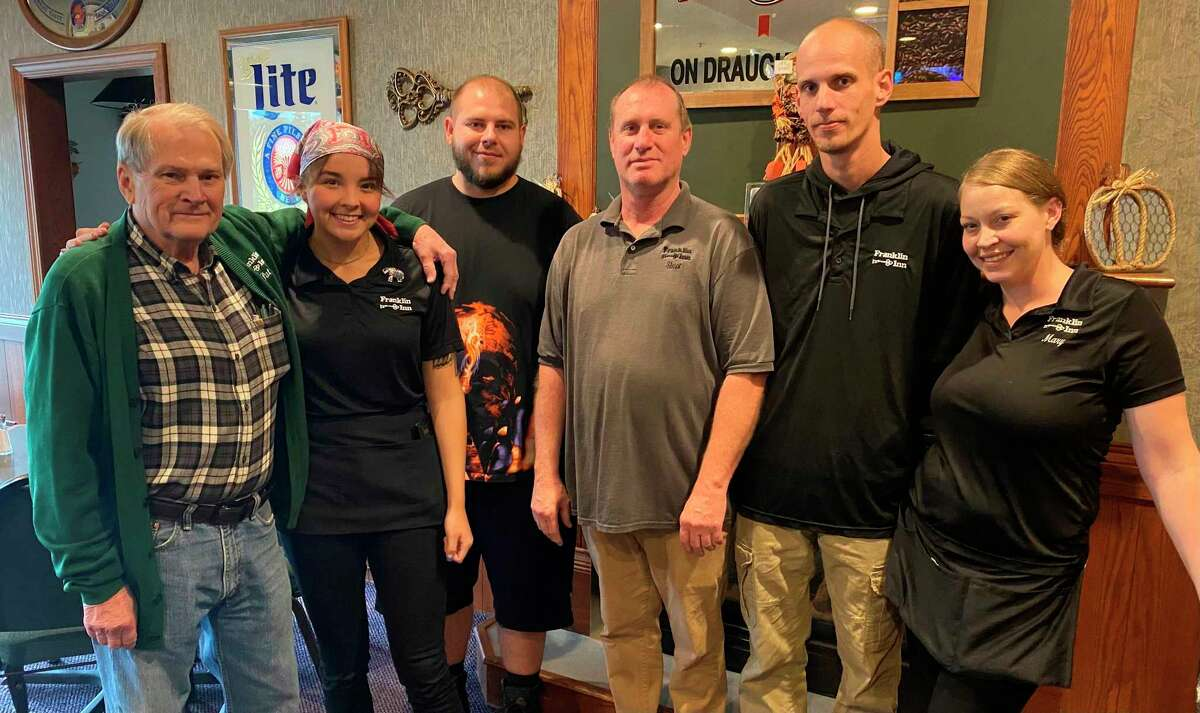Pat Lerash, left, owner of the Franklin Inn Motor Lodge and Banquet Center in Bad Axe, poses with staff members in the Franklin Inn Lounge. Lerash is looking to get his business back to pre-COVID levels as the pandemic winds down. (Mark Birdsall/Huron Daily Tribune)