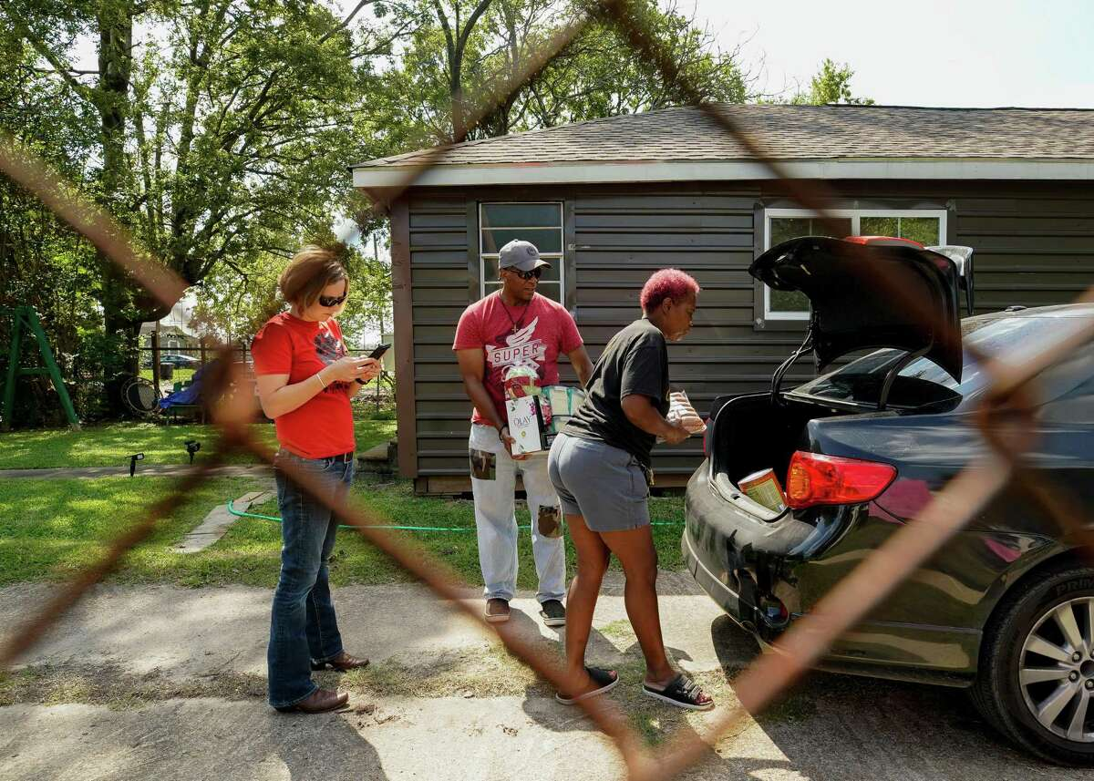 Sandra Edwards, center, unloaded groceries from the trunk of her car as she hosted a barbecue at her house in an effort to raise money to fix up her house, on Wednesday, Oct. 6, 2021, in Fifth Ward. Edwards' home was damaged during Hurricane Harvey and is located in the polluted site near Union Pacific's railway station.