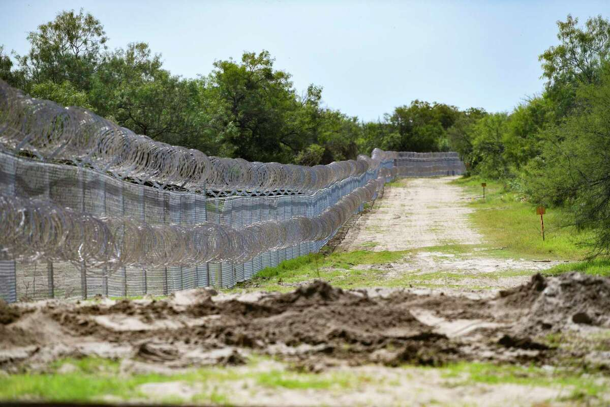 """The """"Abbott fence,"""" made of chain link and concertina wire, has been placed along the border at Del Rio, Texas, on Wednesday, July 28, 2021. Texas Gov. Greg Abbott has sent the Texas National Guard and Department of Public Safety troopers to stop the migration."""