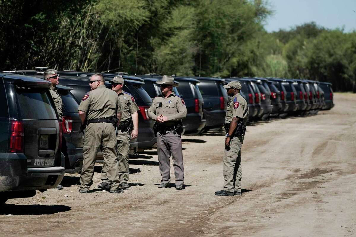 Texas Department of Public Safety officials stand near a lineup or vehicles parked near an encampment under the Del Rio International Bridge where migrants, many from Haiti, have been staying after crossing the Rio Grande, Thursday, Sept. 23, 2021, in Del Rio, Texas. (AP Photo/Julio Cortez)