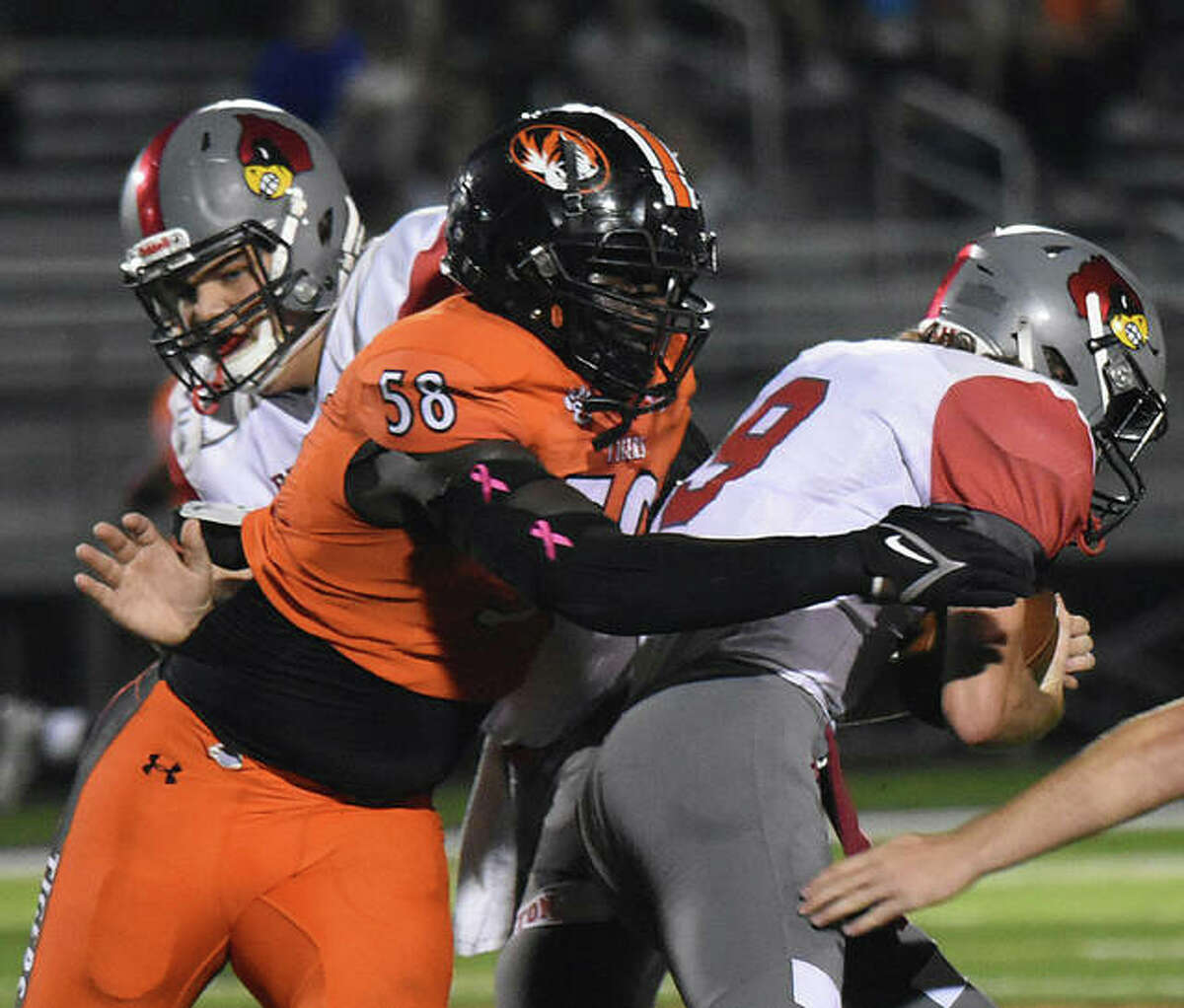 Edwardsville defensive tackle Nasim Cairo pulls down Alton quarterback Grant McAfoos for one of his four sacks.
