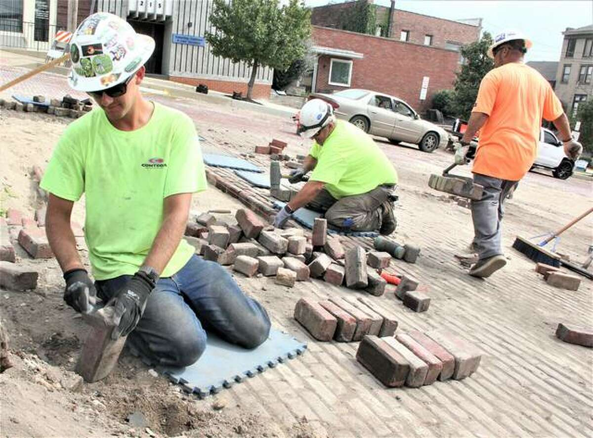 Terry Dann McBride, left, a worker for MAV Masonry in Marissa, cleans off bricks before they are tamped back into place on Market Street in Alton in front of the Stratford Hotel. The bricks are being reset after being removed for a sewer replacement project.