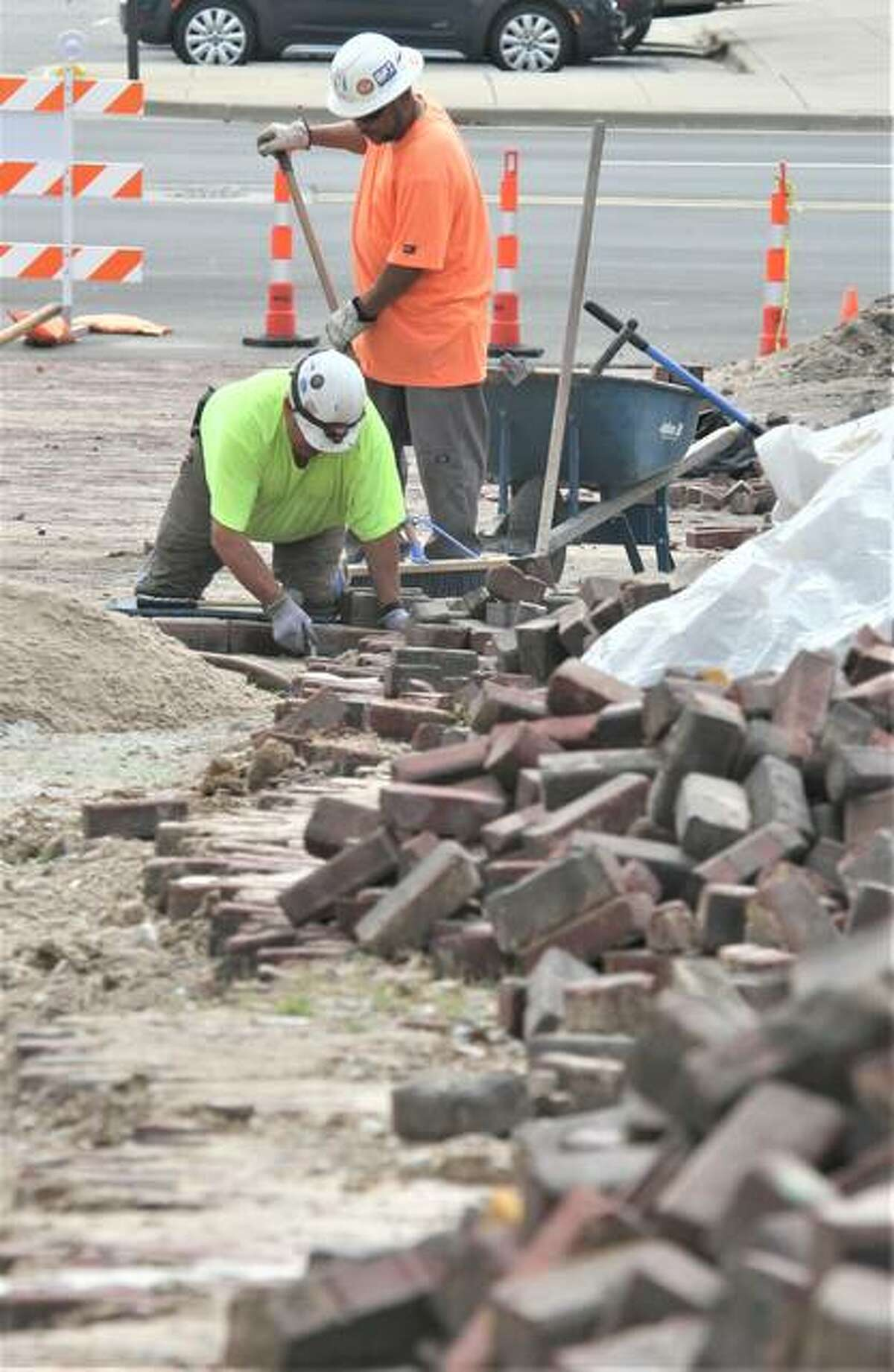 Workers for MAV Masonry replace paving bricks on Market Street in Alton Thursday afternoon in front of the Stratford Hotel. The bricks are being reset after being removed for a sewer replacement project.