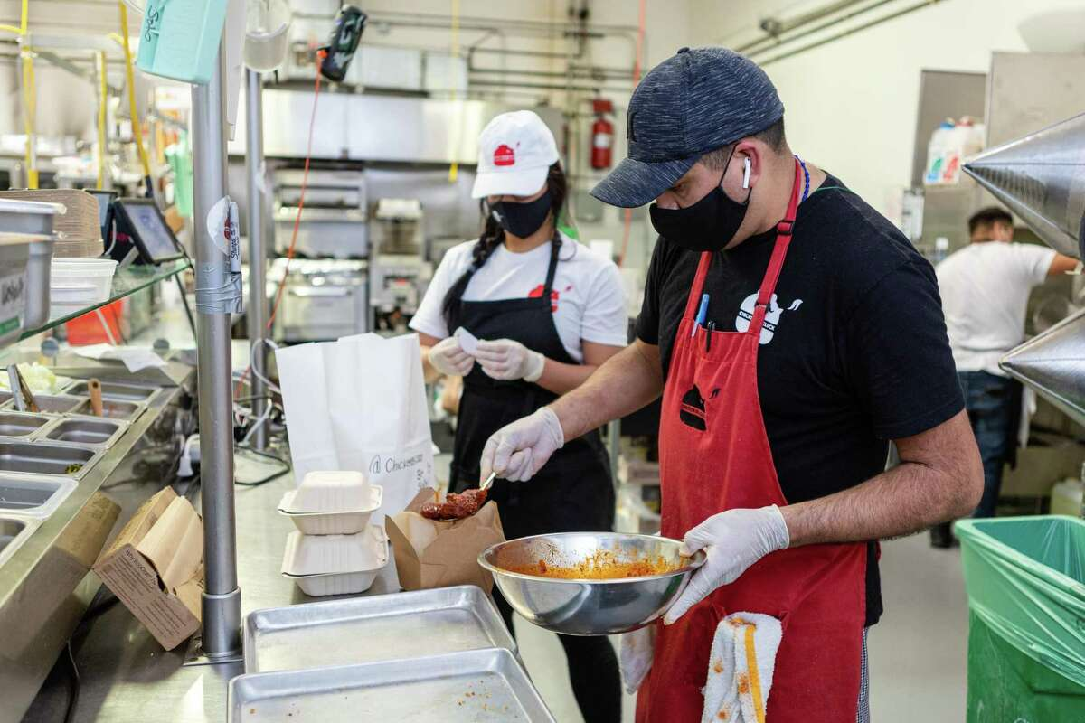 Eduardo Soto (right), kitchen manager, and Bua Vanitsthian, owner of Chicken as Cluck, pack an order for pickup in San Francisco in May 2020. People must continue to wear masks at San Francisco restaurants when not eating or drinking under city rules.