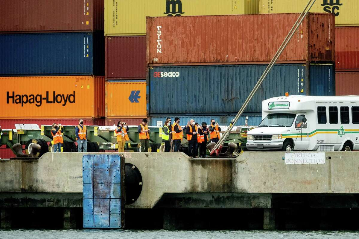 People photograph the Rotterdam Express as it unloads containers in Oakland, Calif., on Wednesday, Oct. 6, 2021.