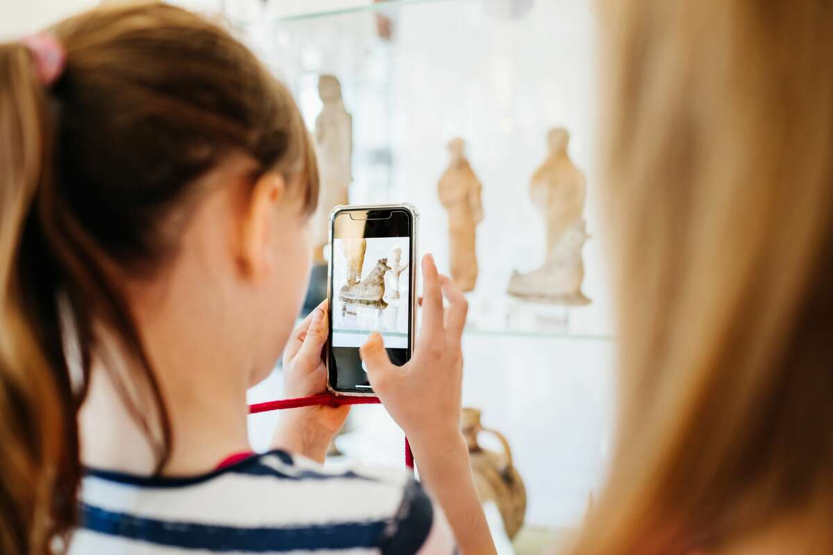 A young girl taking some photos of an exhibit using her smartphone while on a field trip with her classmates.