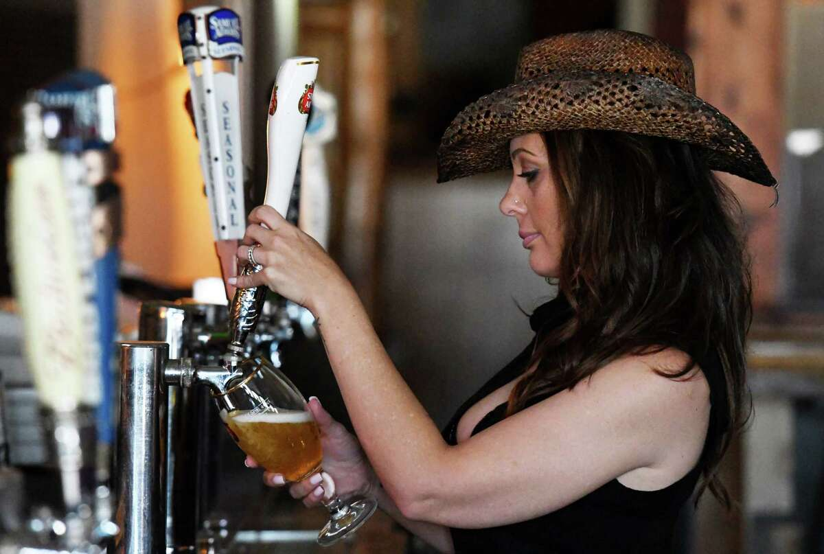 Side Door Café manager and bartender Brandy Karczewski attends to the afternoon customers on Thursday, Oct. 7, 2021, at the Side Door Café on Western Ave. in Guilderland, N.Y. The bar has been closed since April 2020 and just opened last week with a new western theme.