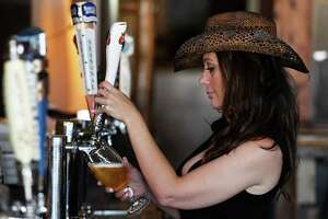 Side Door Café manger and bartender Brandy Karczewski attends to the afternoon customers on Thursday, Oct. 7, 2021, at the Side Door Café on Western Ave. in Guilderland, N.Y. The bar has been closed since April 2020 and just opened last week with a new western theme.