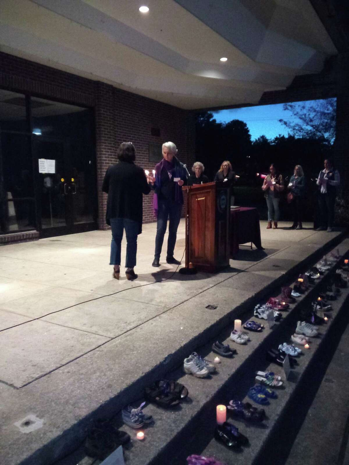 The Susan B. Anthony Project held its annual domestic violence awareness vigil Wednesday night at Coe Memorial Park. State Rep. Maria Horn, center, lights a candle during the vigil after reading a victim's name.