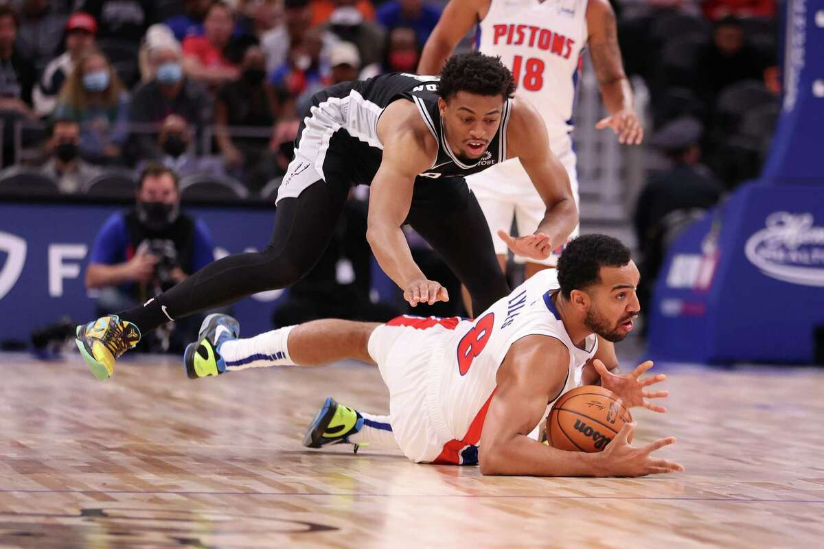 DETROIT, MICHIGAN - OCTOBER 06: Trey Lyles #8 of the Detroit Pistons dives for the ball in front of Keldon Johnson #3 of the San Antonio Spurs during a preseason game at Little Caesars Arena on October 06, 2021 in Detroit, Michigan. NOTE TO USER: User expressly acknowledges and agrees that, by downloading and or using this photograph, User is consenting to the terms and conditions of the Getty Images License Agreement. (Photo by Gregory Shamus/Getty Images)